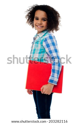 Cute school girl with red colored notebook - stock photo