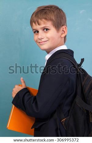 Cute schoolboy is holding an orange book against school blackboard - stock photo