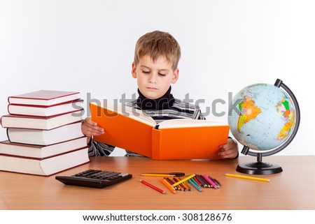 Cute schoolboy is reading a book isolated on a white background - stock photo