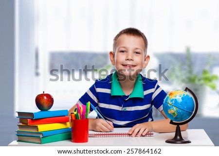 Cute schoolboy is writing in classroom - stock photo