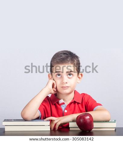 Cute schoolboy lost in his thoughts - stock photo