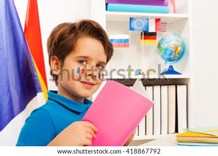 Cute schoolboy reading a book sitting at the desk - stock photo
