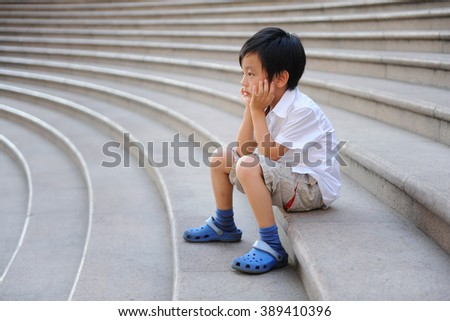 Cute schoolboy sitting on the stairs - stock photo