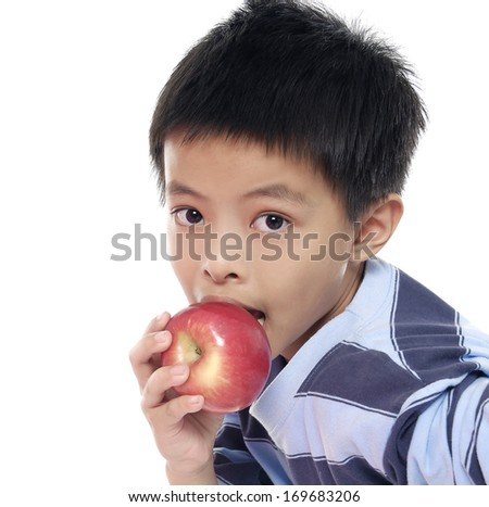 cute schoolboy with and apple looking at camera - stock photo