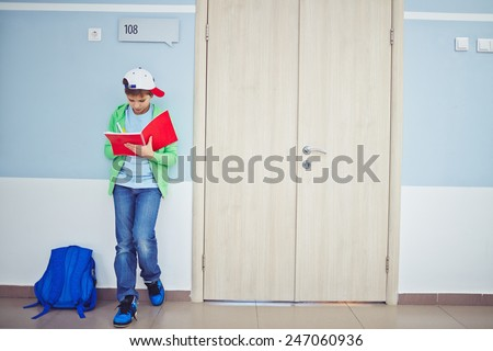 Cute schoolboy writing notes in exercise-book while standing by classroom door - stock photo
