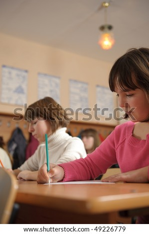 Cute schoolchildren are writing using pencils during lesson - stock photo