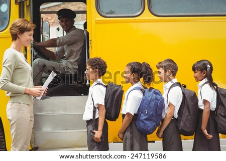 Cute schoolchildren waiting to get on school bus outside the elementary school - stock photo