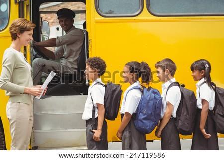 Cute schoolchildren waiting to get on school bus outside the elementary school - stock photo