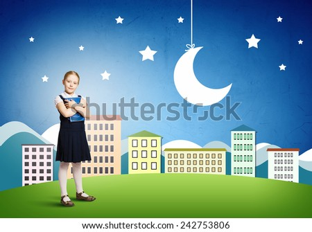 Cute schoolgirl against colorful background with book in hands - stock photo
