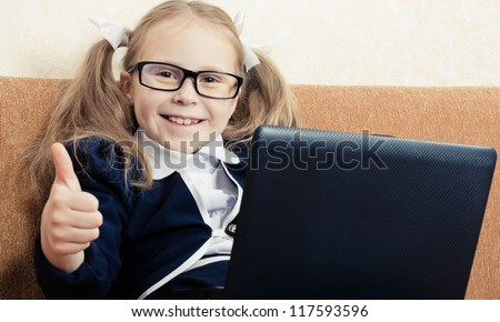 Cute schoolgirl in glasses with a laptop shows gesture okay. - stock photo