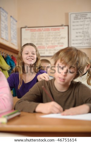 Cute schoolgirl is trying to attract attention of her classmate - stock photo