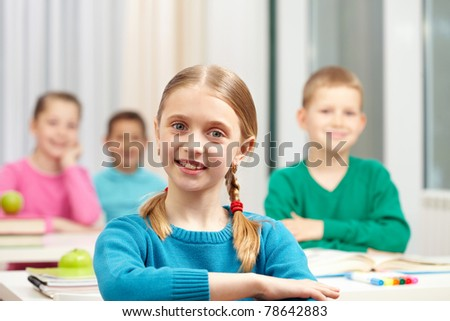 Cute schoolgirl looking at camera on background of her classmates - stock photo