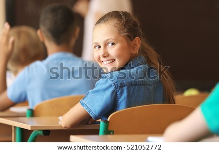 Cute schoolgirl on lesson in classroom
