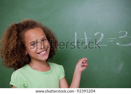 Cute schoolgirl pointing at an addition on a blackboard - stock photo
