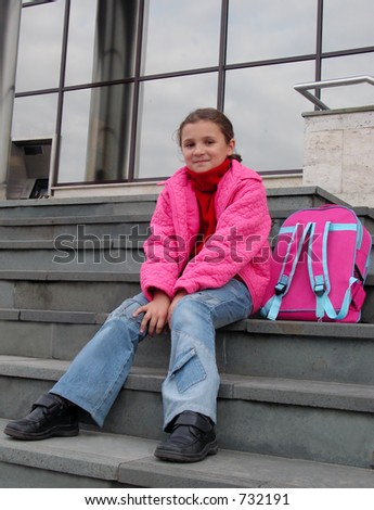 Cute schoolgirl sitting on a corporate building steps.