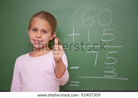 Cute schoolgirl with the thumb up in front of a blackboard - stock photo