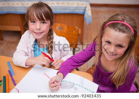 Cute schoolgirls drawing in a coloring book in a classroom