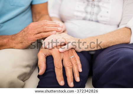 Cute senior couple holding hands on sofa - stock photo