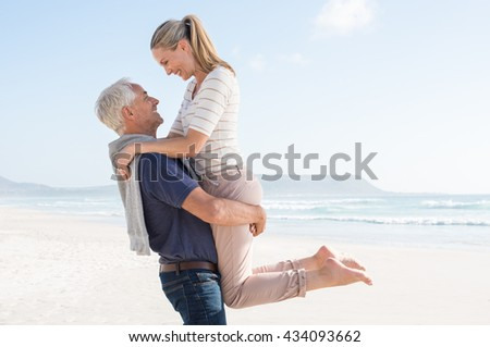 Cute senior couple hugging on the beach on a sunny day. Happy couple having fun together at the beach. Senior man carrying her wife at beach and looking at each other. - stock photo
