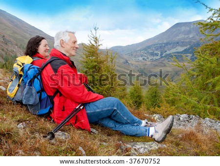 cute seniorcouple hiking in an autumn mountainlandscape - stock photo