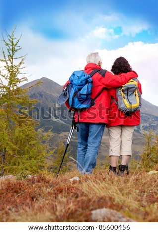 cute seniorcouple hiking in an autumn mountainlandscape. upright format. - stock photo