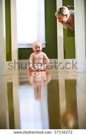 Cute seven month old chubby baby wearing diaper sitting on floor laughing at mother - stock photo