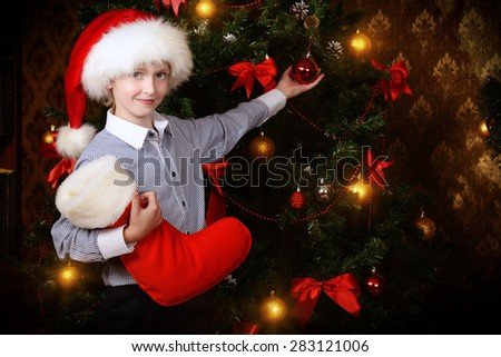 Cute seven year old boy stands with gifts by the fireplace at home. The magic of Christmas. - stock photo