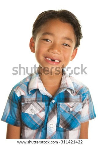 Cute Seven Year Old Filipino Boy On a white Background Smiling and Showing the gap where his two front teeth are missing, - stock photo