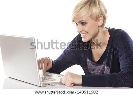cute short hair smiling blonde working on a laptop on white background