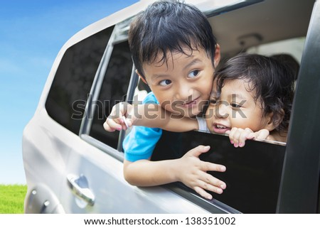 Cute sibling in car during road trip - stock photo