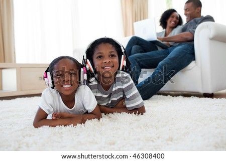 Cute siblings listening music lying on the floor in the living room - stock photo
