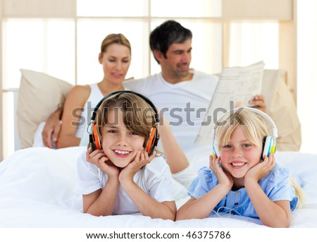 Cute siblings listening music with headphones lying on bed