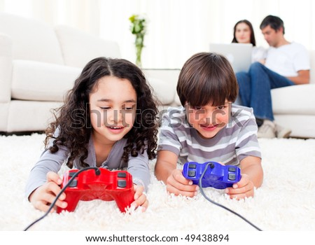 Cute siblings playing video games laying down on the floor in the living room - stock photo