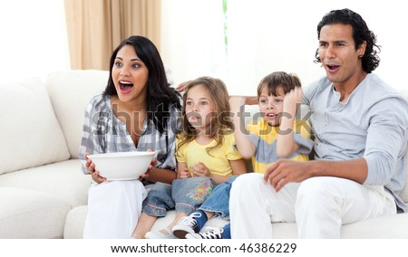 Cute siblings watching TV with their parents in the living room - stock photo