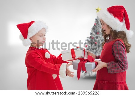 Cute siblings with gifts against christmas tree in bright room - stock photo
