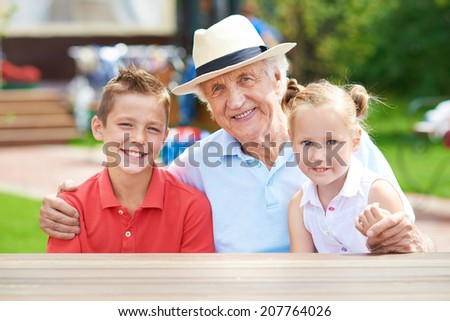 Cute siblings with their grandfather looking at camera at weekend outdoors - stock photo