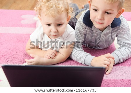 Cute sister and brother lying on floor with laptop