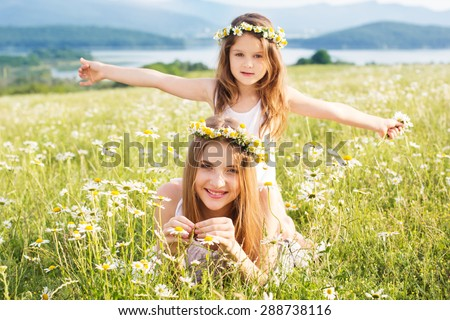 Cute sisters girls are wearing white dresses at  green camomile field with mountains view - stock photo