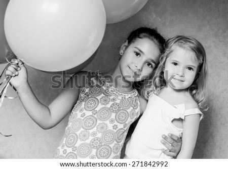 cute sisters with balloons house  ( black and white ) - stock photo