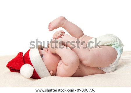 cute six month old baby boy in christmas hat playing with his feet, isolated on white background - stock photo