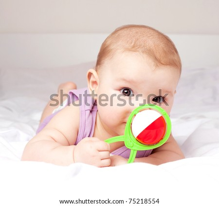 cute six months old baby on the bed with a toy - stock photo