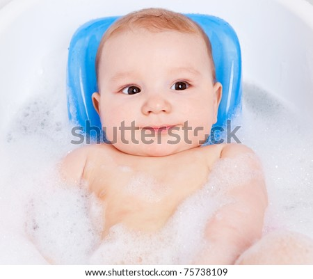 cute six months old baby taking a relaxing bath with foam - stock photo