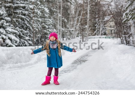 Cute six year old girl dressed in a blue coat and a pink hat and boots, hamming and playing in the winter forest - stock photo