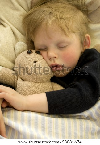Cute sleeping child cuddling teddy bear - stock photo