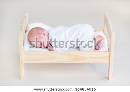 Cute sleeping newborn baby in a toy bed - stock photo