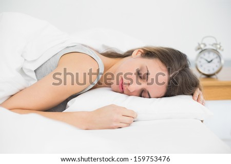 Cute sleeping woman lying in her bed under the cover at home - stock photo