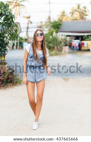 Cute slim tanned girl standing near tree in a park. She wears white t-shirt, denim shorts, white sneakers and black sunglasses. She has long dark straight hair. She smiles widely.  - stock photo
