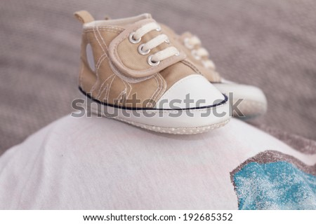 Cute small boots on the pregnant belly - stock photo