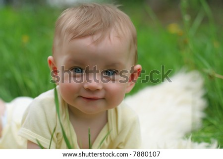 Cute small boy in green grass - he smiles and has fun - stock photo