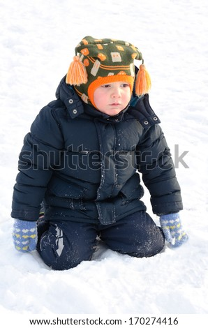 Cute small boy kneeling in winter snow wrapped up warmly in a thick jacket and woolly cap as he watches something out of frame - stock photo